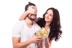 Frau mit dem großen toothy Lächeln, das Freunde hält, mustert, ihm ein Geschenk für Valentinstag gebend Lizenzfreies Stockbild