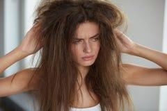 Frau mit dem Halten des lang schädigenden trockenen Haares Haar-Schaden, Haarpflege lizenzfreies stockfoto