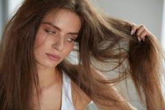 Frau mit dem Halten des lang schädigenden trockenen Haares Haar-Schaden, Haarpflege stockfotografie
