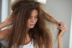 Frau mit dem Halten des lang schädigenden trockenen Haares Haar-Schaden, Haarpflege stockfotos