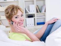 Frau mit dem Handy, der zu Hause entspannt Lizenzfreie Stockfotos
