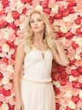 Frau mit dem Hintergrund voll von den Rosen Stockbild