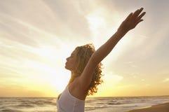 Frau mit dem Hände angehobenen Meditieren am Strand Lizenzfreies Stockfoto