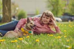 Frau mit dem Hund, der auf dem grünen Gras liegt Lizenzfreie Stockfotografie