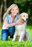 Frau mit dem Hund, der auf dem Gras sitzt Lizenzfreie Stockfotografie