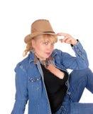Frau mit dem Hut, der auf Boden sitzt Stockfotos