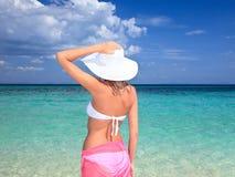 Frau mit dem Hut, der auf dem Strand steht lizenzfreie stockbilder