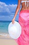 Frau mit dem Hut, der auf dem Strand steht Stockfotos