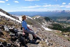 Frau mit dem Hut, der auf Felsen Bergblick genießend sitzt Lizenzfreie Stockbilder