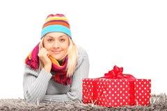 Frau mit dem Hut und Halsbekleidung, die auf einem Teppich nahe Geschenk liegen Stockfotografie
