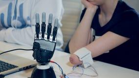 Frau mit dem innovativen kybernetischen bionischen Arm Behinderte Frau betreibt moderne bionische Prothese stock footage