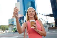 Frau mit dem Kaffee, der selfie durch Smartphone nimmt Lizenzfreie Stockfotos