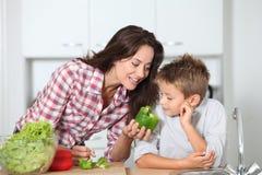Frau mit dem Kind, das Gemüse kocht Stockbilder