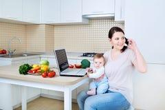 Frau mit dem Kind, das Lebensmittel zubereitet und am Telefon spricht stockfotografie