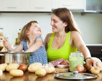 Frau mit dem Kind, das Suppe kocht Stockfoto