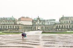 Frau mit dem Kind, das weg von dem Regen in Dresden läuft Stockfotos