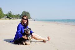 Frau mit dem kleinen Hund auf dem Strand Stockfoto