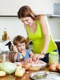 Frau mit dem kleinen Mädchen, das an der Küche kocht lizenzfreie stockbilder