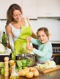 Frau mit dem kleinen Mädchen, das zu Hause kocht Stockbilder