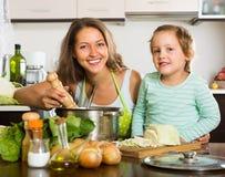 Frau mit dem kleinen Mädchen, das zu Hause kocht Stockfotografie