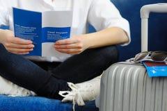Frau mit dem Koffer geht auf eine Reise Lesen Sie Reiseversicherung lizenzfreies stockbild