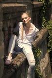 Frau mit dem langen blonden Haar, Frisur auf sonnigem im Freien Frau im Hemd und Jeans sitzen auf Steinwand, Mode Art und Weise Stockbilder