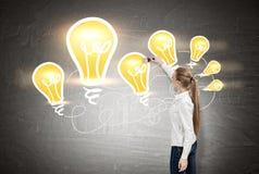 Frau mit dem langen blonden Pferdeschwanz, der gelbe Glühlampen zeichnet Stockfotos