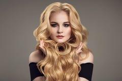 Frau mit dem langen gelockten schönen Haar Stockfotografie