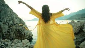 Frau mit dem langen Haar, das auf felsigem Ufer und Erhöhungen seine Hände steht stock video footage