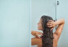 Frau mit dem langen Haar, das Dusche nimmt. Hintere Ansicht stockfoto