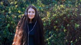 Frau mit dem langen Haar in hörender Musik der Kopfhörer an einem sonnigen, windigen Tag stock video