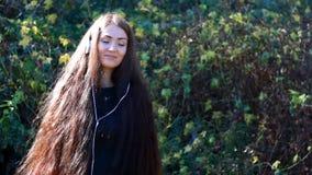 Frau mit dem langen Haar in hörender Musik der Kopfhörer an einem sonnigen, windigen Tag stock footage