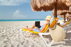 Frau mit dem Laptop, der auf dem deckchair sich entspannt Stockfoto