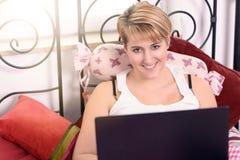 Frau mit dem Laptop, der auf Kissen auf dem Bett sich lehnt Stockfotos