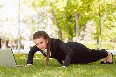 Junge Frau mit dem Laptop, der im grünen Gras liegt Stockbilder