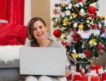 Frau mit dem Laptop, der nahe Weihnachtsbaum sitzt stockbilder