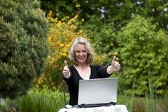 Frau mit dem Laptop, der oben beide Daumen aufwirft Stockbild