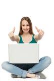 Frau mit dem Laptop, der sich Daumen zeigt Stockfotos