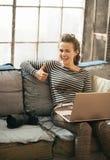 Frau mit dem Laptop, der sich Daumen zeigt Stockfotografie