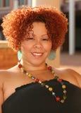 Frau mit dem lockigen roten Haar und den hellen Schmucksachen Lizenzfreie Stockfotografie