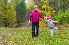 Frau mit dem Mädchen, das Aerobic im Herbstpark tut Stockbild