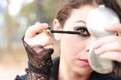 Frau mit dem Make-up, das im Spiegel schaut Stockfotografie