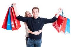 Frau mit dem Mann, der Bündel Einkaufstaschen hält stockfotografie