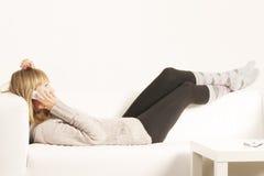 Frau mit dem Mobiltelefon, das auf Sofa legt Lizenzfreie Stockfotos