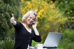 Frau mit dem Mobiltelefon und Laptop, die oben Daumen aufwerfen Stockfoto