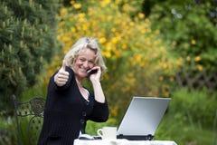 Frau mit dem Mobiltelefon und Laptop, die oben Daumen aufwerfen Stockfotografie