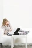 Frau mit dem Mobiltelefon und Zeitschrift, die auf Sofa legen Lizenzfreie Stockfotografie