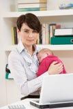 Frau mit dem neugeborenen Schätzchen, das vom Haus unter Verwendung des La arbeitet Lizenzfreie Stockfotos
