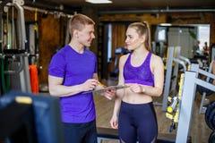 Frau mit dem persönlichen Trainer, der Trainingsplan in der Turnhalle erstellt stockfoto