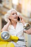 Frau mit dem rührenden Haar des Telefons Lizenzfreie Stockfotografie